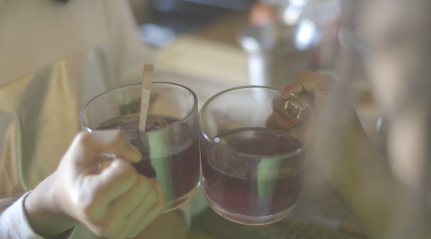 A photograph of two hands holding glass mugs of a purple tea. One has a small spoon in it.