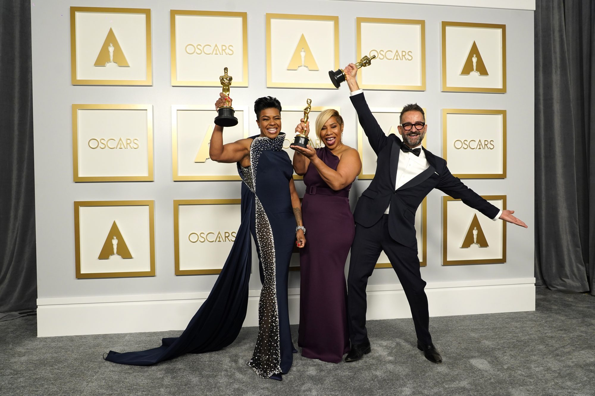Two dark-skinned women and one medium skinned man celebrate in front of the Oscars photo backdrop. They are dressed in fancy evening wear and each hold up an Oscar statue with big smiles on their faces.
