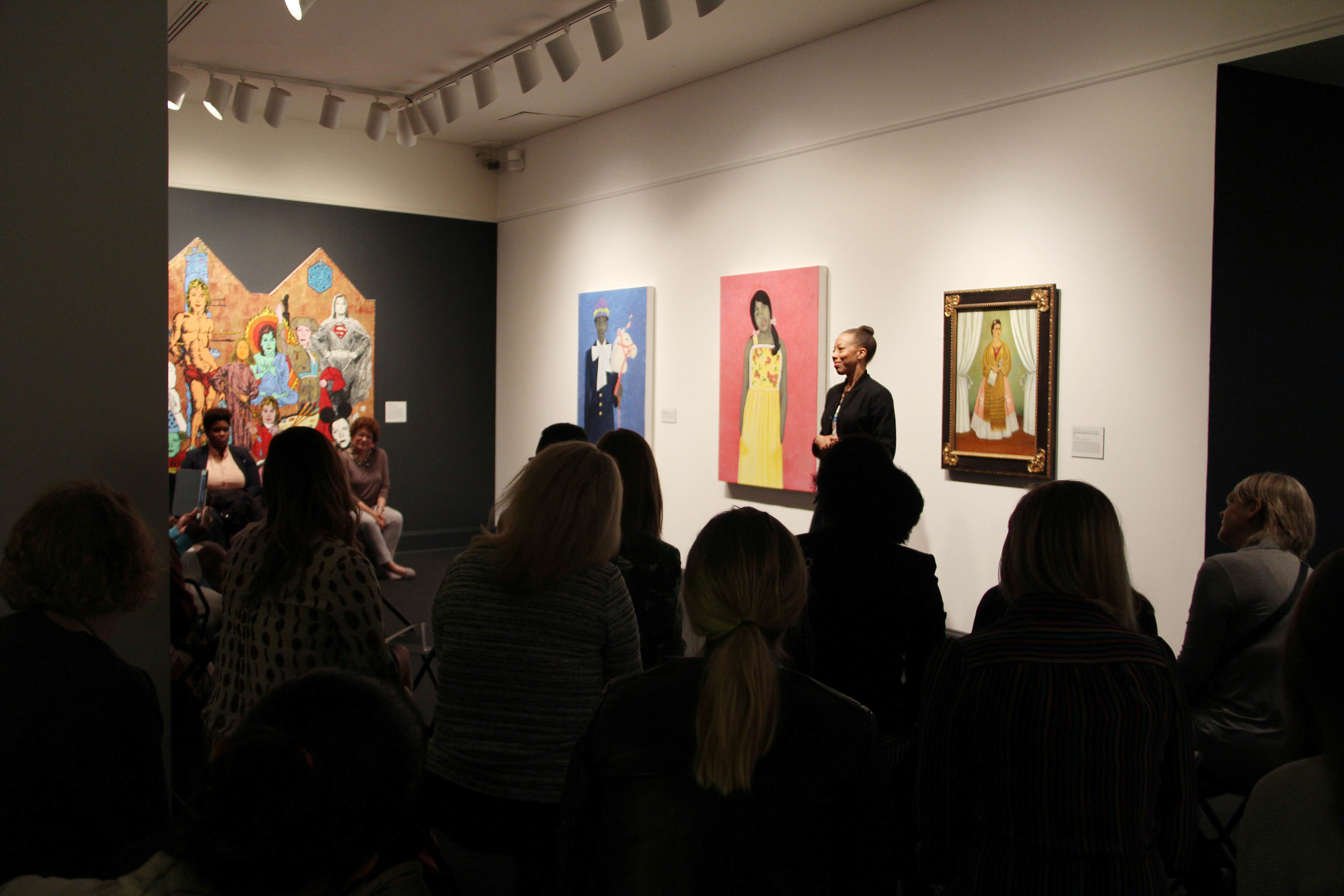 In a museum gallery, a medium-skinned woman stands in front of three striking portraits--two of figures painted in grayscale, another a Frida Kahlo portrait--and speaks to a crowd of people seated on gallery stools.
