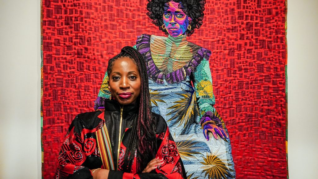 A dark-skinned woman with a high, braided ponytail stands in front of a colorful, fine art quilt depicting an image of a woman wearing a colorfully patterned dress and staring straight at the viewer. The real woman smiles slightly with her arms crossed across a vibrant red and black jacket zipped to her neck.