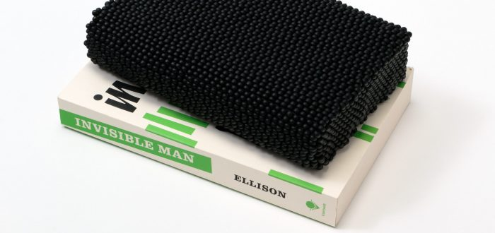 A paperback copy of Ralph Ellison's novel 'Invisible Man' sits on a white surface. The book features black text and short, green, vertical lines on a white background. Atop the book is a book-like shape comprising black beads.