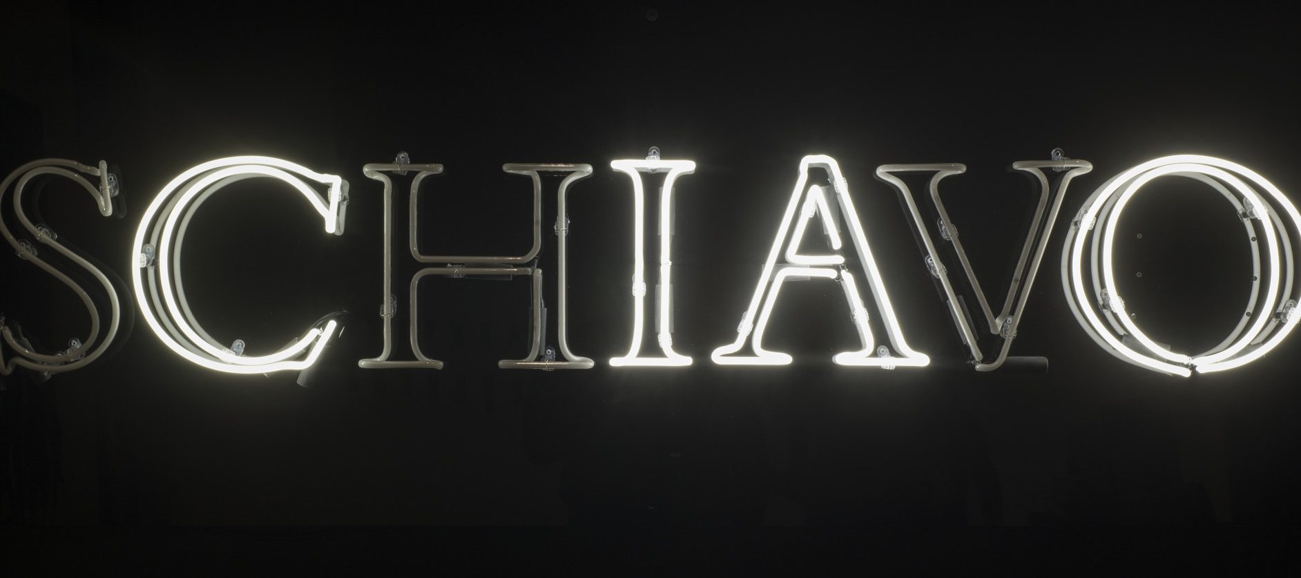 White, capital, neon letters spell the Italian word 'schiavo' in serif text against a black background. The 's,' 'h,' and 'v' are dark, leaving the letters to spell 'ciao.'