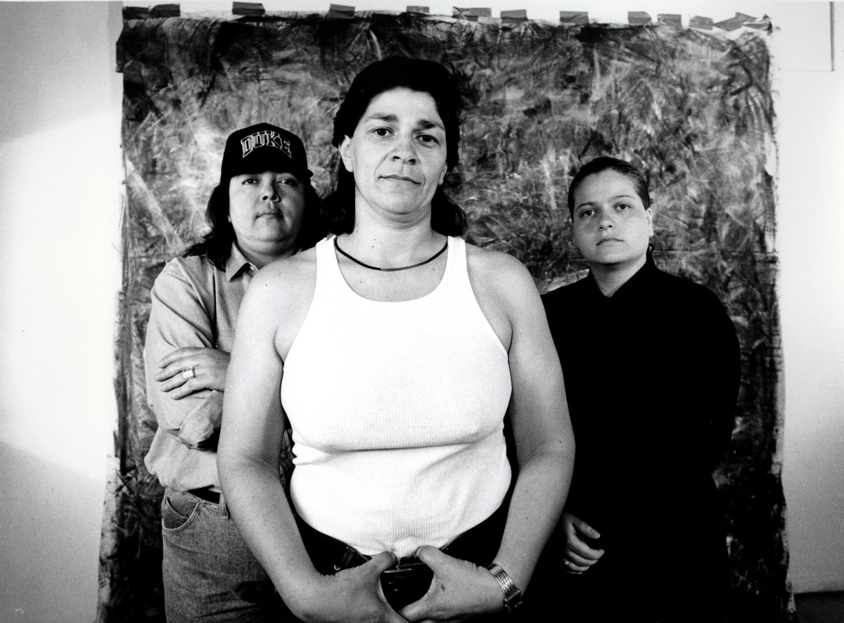 A black-and-white photograph of three Latino/a people standing in front of a taped backdrop. They look at the camera unsmiling and all wear casual clothing.