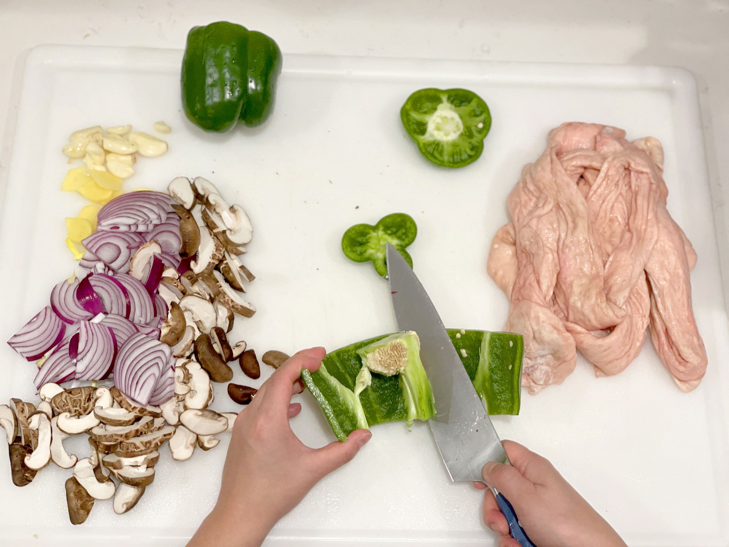 A pair of medium-light skinned hands slice the seeds out of a green pepper using a large knife on a white cutting board, seen from above. To the left is a pile of sliced mushrooms and red onions, and garlic. On the right is the raw skin of a chicken carcass.