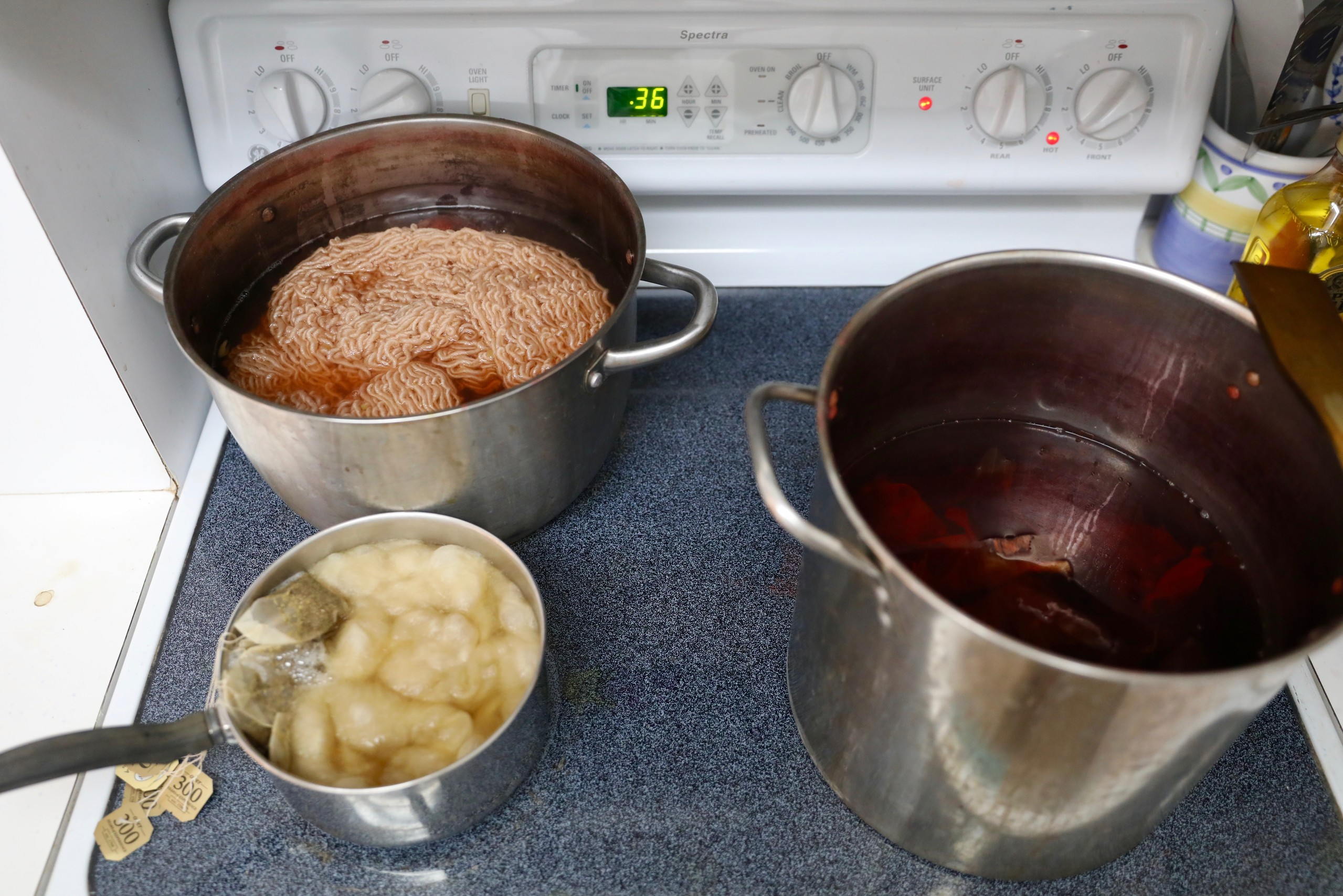 Atop an electric stove, three different sized stainless steel pots are filled with water and yarn or cotton. They are in the process of being dyed by tea bags, berries, and other organic matter.
