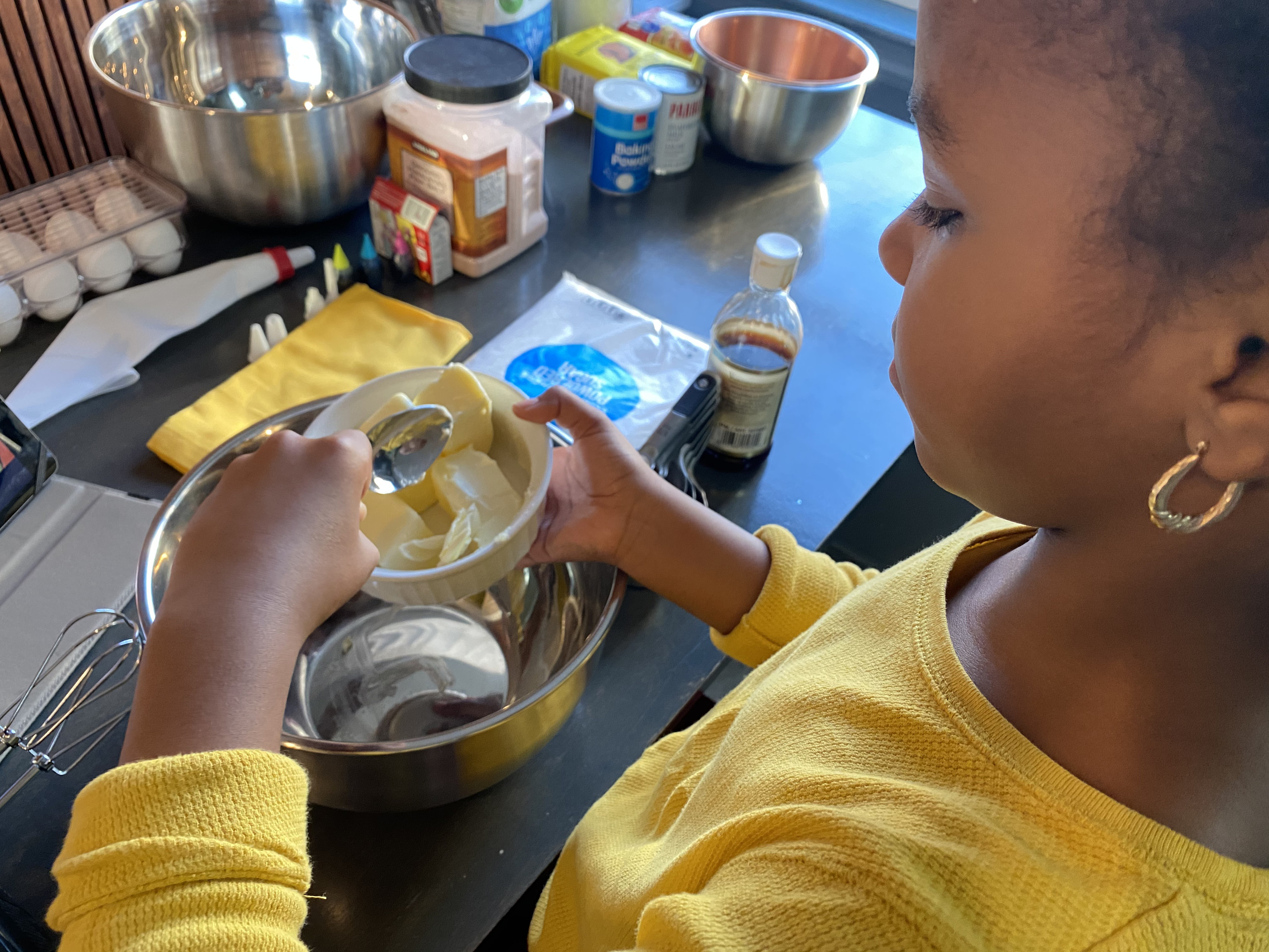 A view from over the shoulder of a medium-dark skinned girl baking at a counter that showcases a wide array of baking ingredients. She scoops chunks of butter into an empty, shiny, silver bowl, and wears earrings and a yellow shirt with sleeves rolled up.