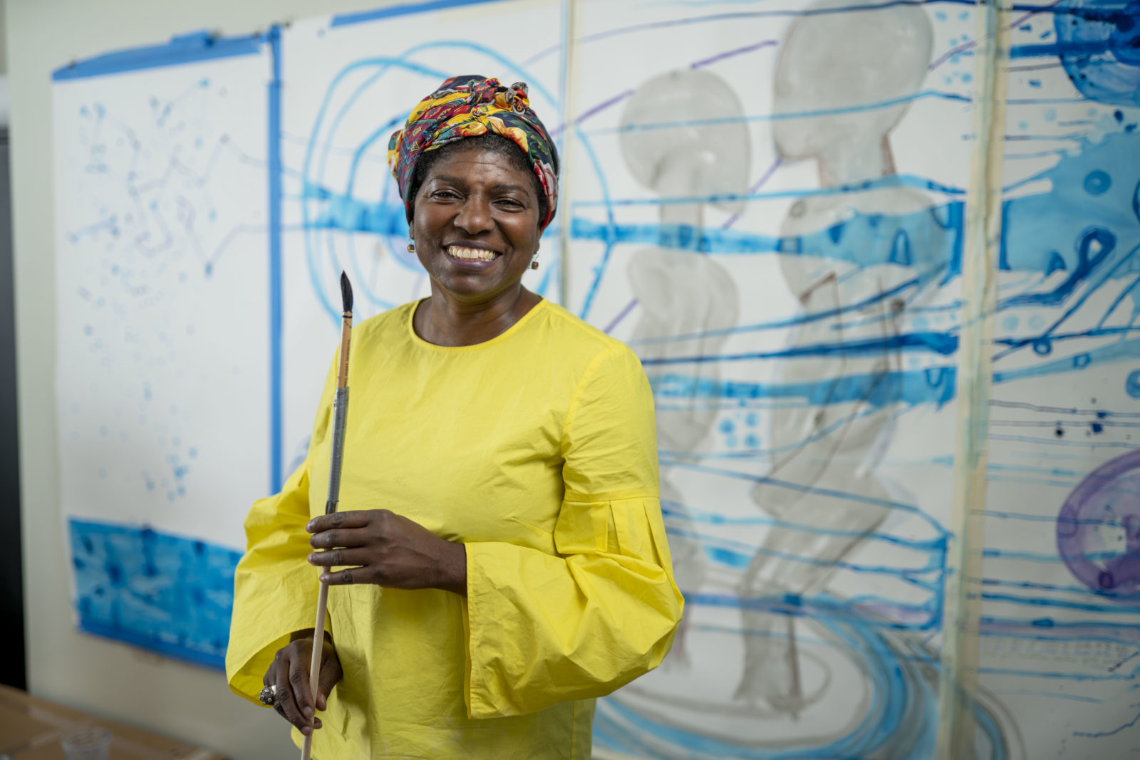 A dark-skinned woman in a bright yellow long barrel-sleeved dress stands in front of a wall of large artworks in process. She wears a colorful headwrap and smiles cheerfully while holding a long paintbrush.