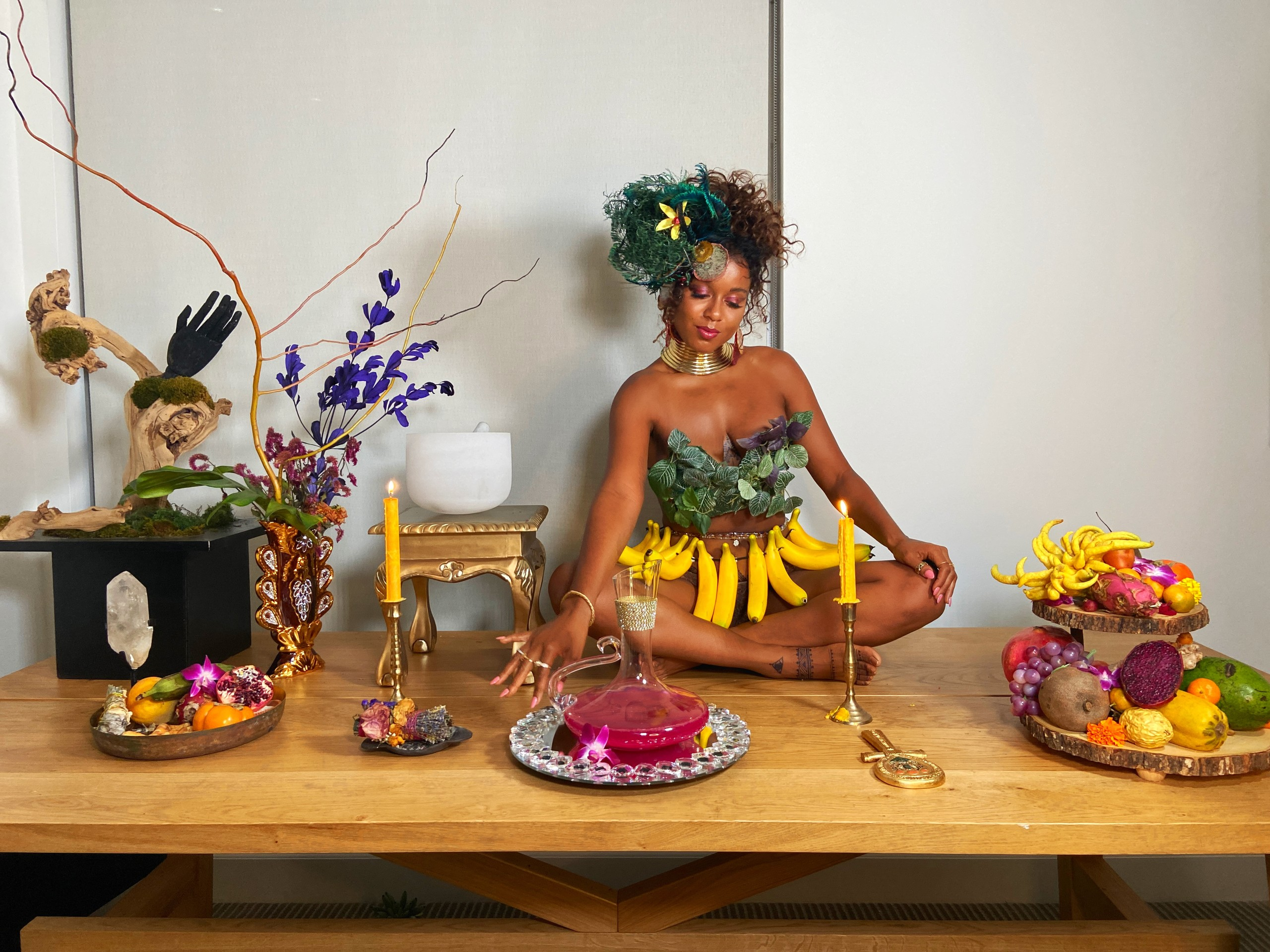 A medium-dark skinned adult woman sits cross-legged on a long wooden table set with platters of colorful fruit, candles, plants, and a pitcher of a pink liquid. She wears green leaves on her chest, gold jewelry, a skirt of bananas, and her hair pulled up with green feathers.