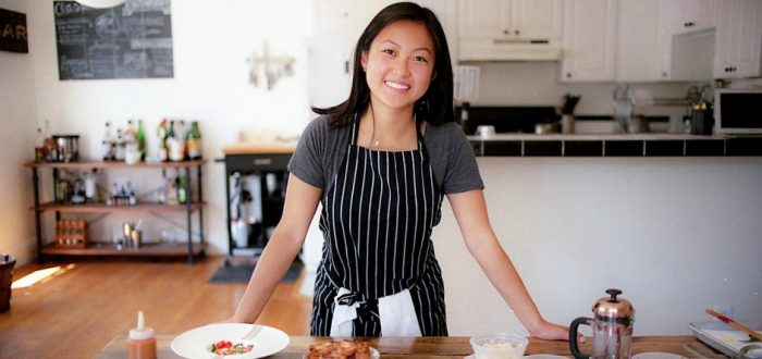 A light-skinned woman of Asian descent stands behind a large, wooden kitchen table that is full of two white dishes of finely plated food and various small, plastic to-go dishes., alongside a small bronze French Press coffee maker. The woman smiles and wears a grey tshirt under a black and white vertical striped apron.