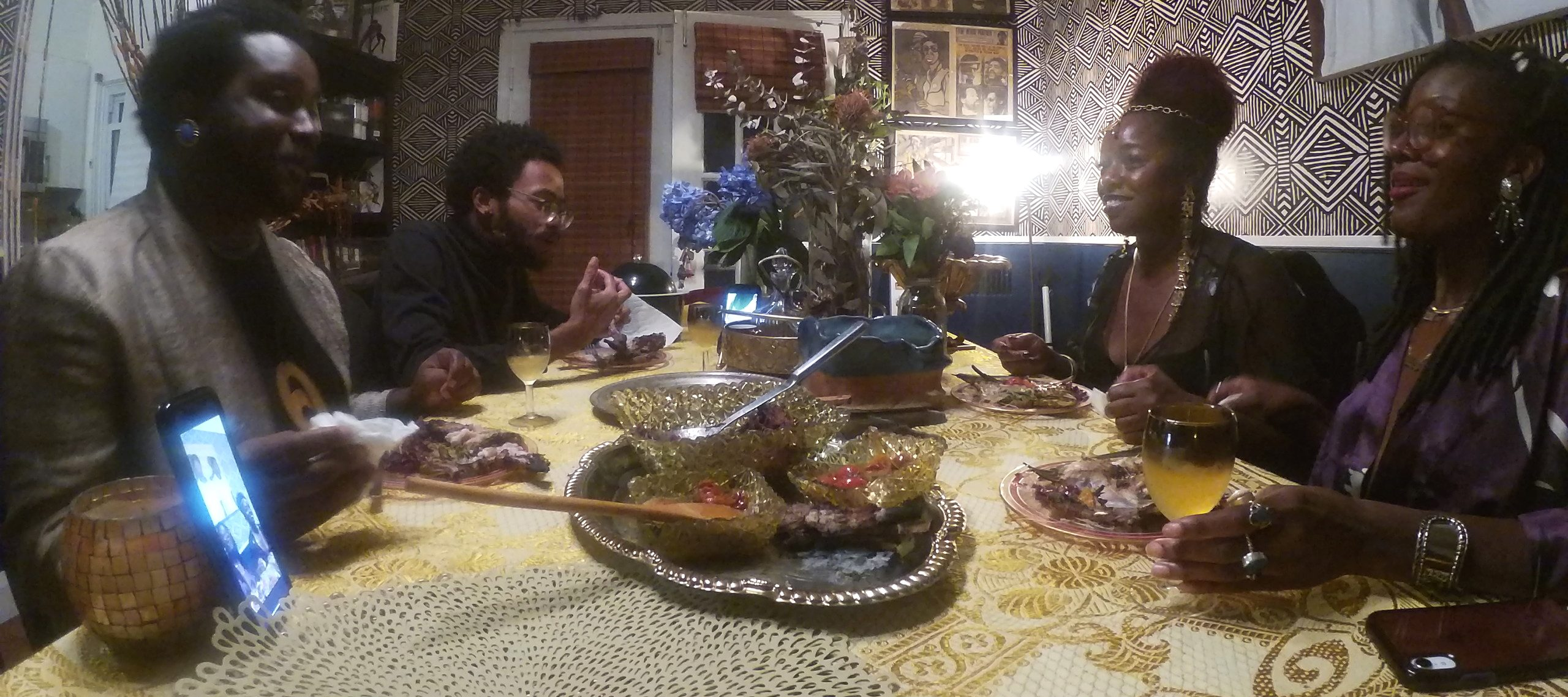 Four dark-skinned adults dressed up in suit jackets, nice tops, and jewelry sit around a table set with a yellow patterned tablecloth and meal, two on each side. A phone stands on the table, displaying other people calling in. The walls are covered in art and patterned wallpaper.