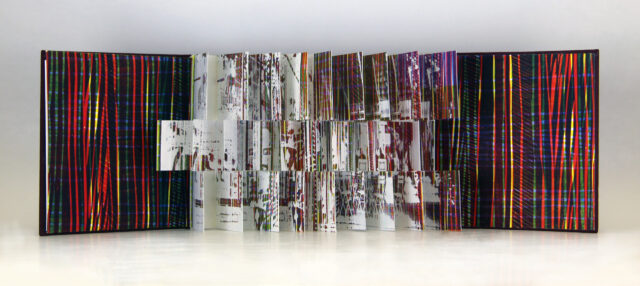 A photograph of an open flag book with red, blue, and yellow diagonal stripes inside the front and back covers. The interior pages are each cut into three sections creating three rows of flags with white splatter paint and multicolored stripes.