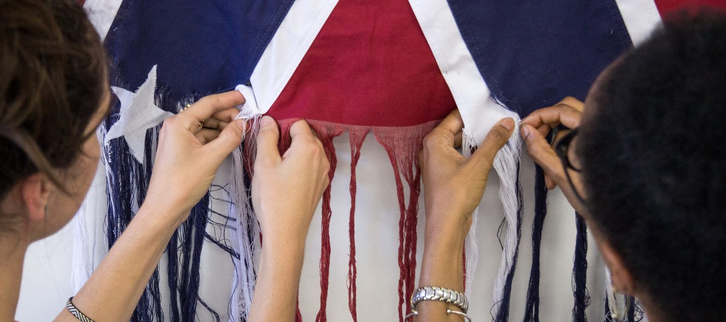 A photograph of two figures standing side by side, unraveling the threads of an American Confederate battle flag. The figure on the left has light skin, and the figure on the right has darker skin. They face away from the camera, with their hands in the center of the image pulling loose the threads.