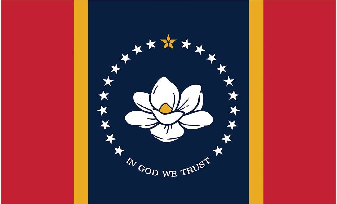 """A state flag features a central, white magnolia with a gold center, surrounded by 20 white stars and a gold five point star at the top. Below the magnolia """"In God We Trust"""" is written in all caps. The stars and magnolia are atop a navy blue background, which is framed by narrow gold stripes on either side, followed by rectangular red stripes on either side of that."""