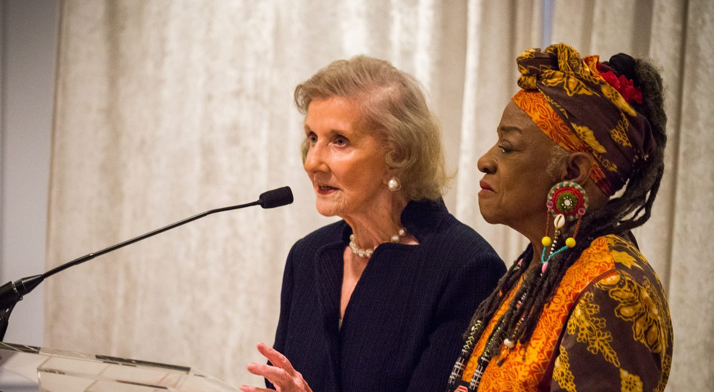 A light-skinned older woman speaks into a black microphone at a podium. Standing next to her is a black woman wearing a colorfully patterned matching headwrap and shirt and large beaded earrings.