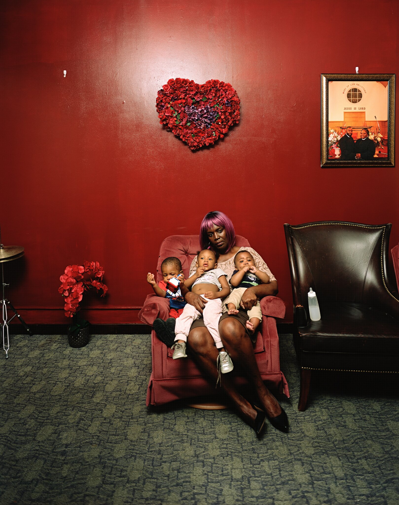 A dark-skinned woman sits on a velvet, mauve recliner chair holding three medium-skinned babies in her lap, all around the ages of 1 to 2. The wall behind her is painted a dark, shiny red, and above her a heart made from flowers hangs as a centerpiece.