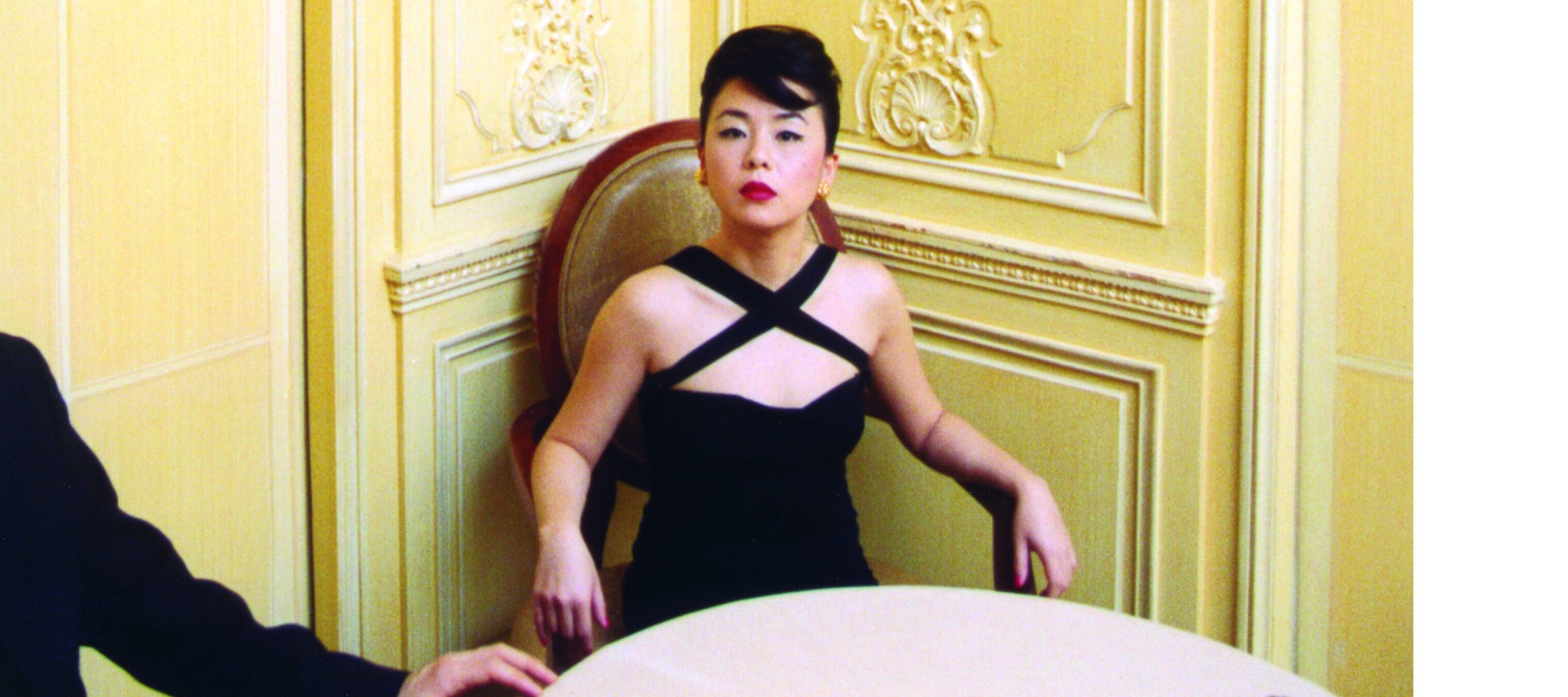 A light-skinned woman of Asian descent is dressed up in a fancy black dress, sitting at a table in a room with ornate yellow walls. Her hair is in an updo. She stares unsmiling at the camera, to her left is a male companion in a suit, thought he has been cut from the frame and all that shows his is arm and half is body.