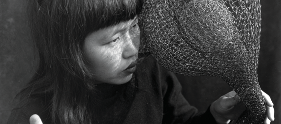 A black-and-white photograph of Ruth Asawa holding one of her large, wire crochet sculptures, draped over her shoulder and in both hands. She is a light-skinned, Asian, adult woman with black hair and blunt bangs.