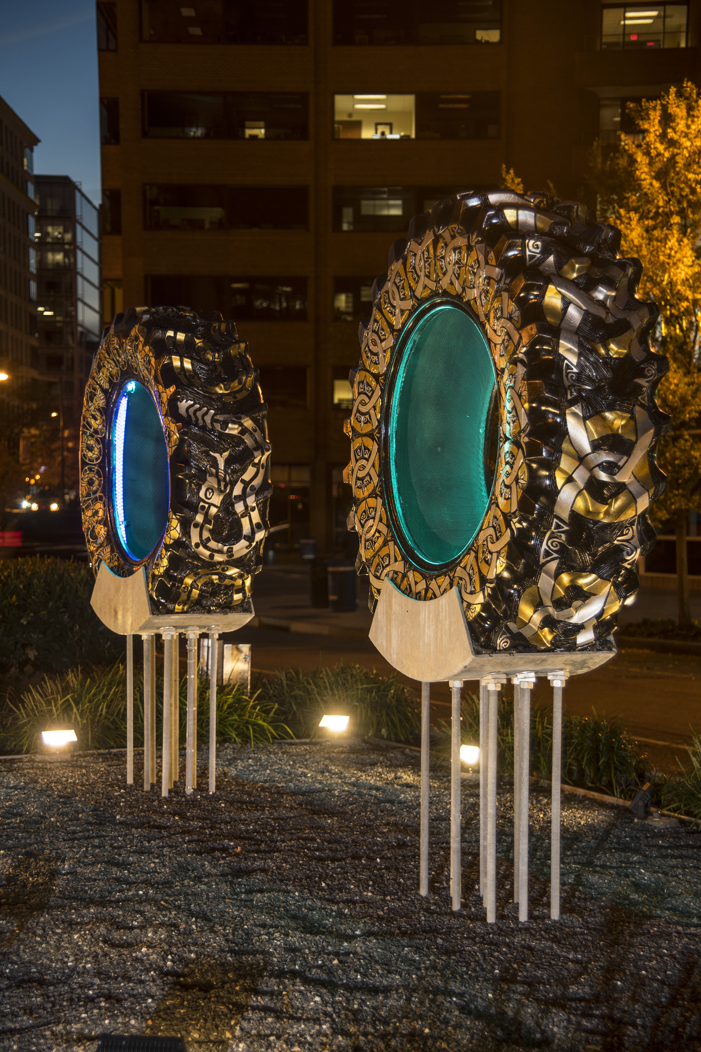 Two large tractor tires are displayed on silver legged pedestals in a center road median of a city street. Each tires is engraved with different designs: one with a snake and the other with a chain pattern. Both are designs are painted silver and gold. Blue lights placed in the interior circle of the tires light the structures up.