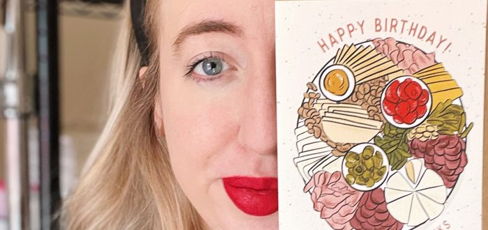 """A light-skinned woman with straight blonde held back with a black head band holds up an illustrated Happy Birthday card that features a platter of meat, veggies, dip, nuts, cheese, and bread. It says """"Let's Eat Fancy Snacks."""""""