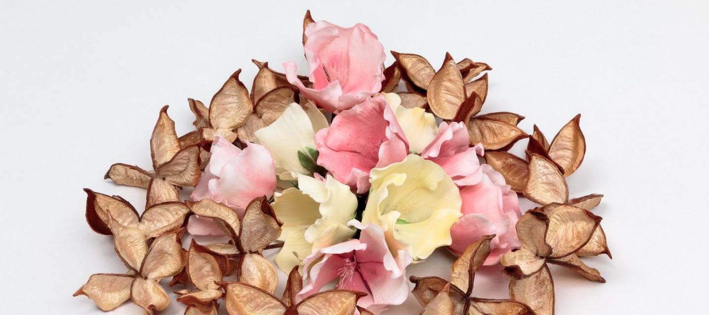 A ring of opened, delicate, pale brown cotton pods surrounding a small pile of creamy white and pastel pink flowers made of sugar.
