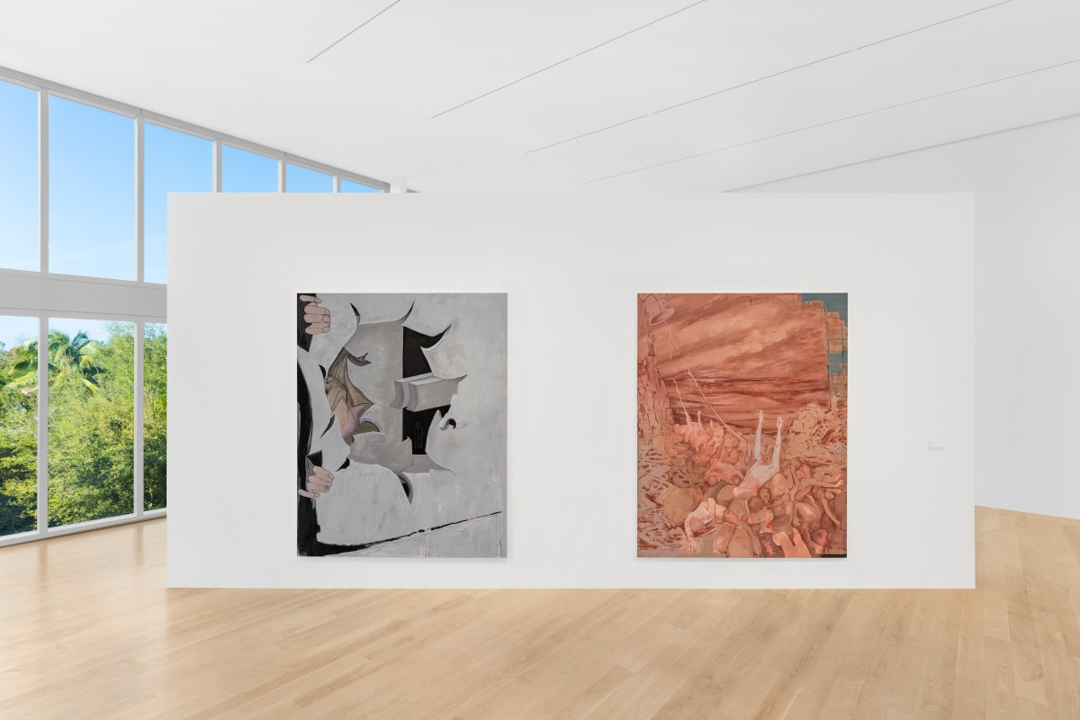 A large, airy gallery room with light wooden floors. A white, pop-up wall in the middle of the room features two abstract paintings. To the left is a wall of floor-to-ceiling windows that look out on green trees and a clear, blue sky.