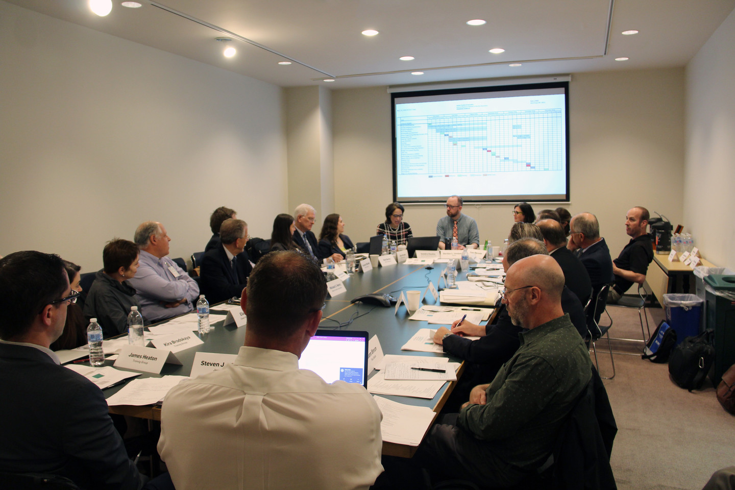 Multiple people attend a meeting around a large rectangular conference table.
