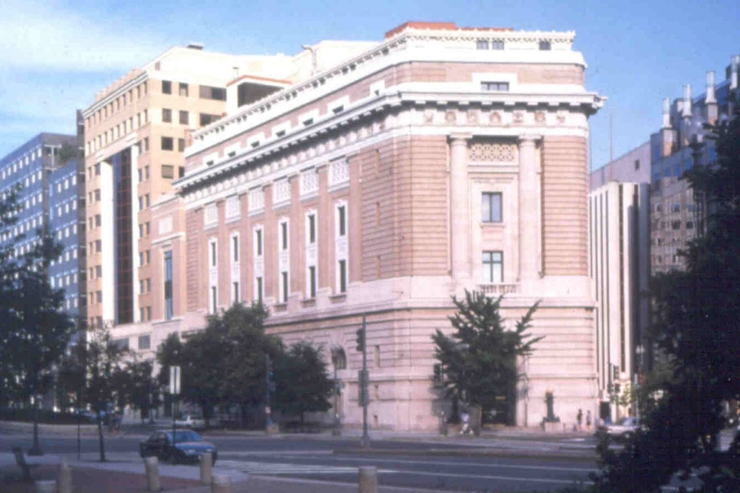 An older color photograph of the building exterior with trees in the foreground.