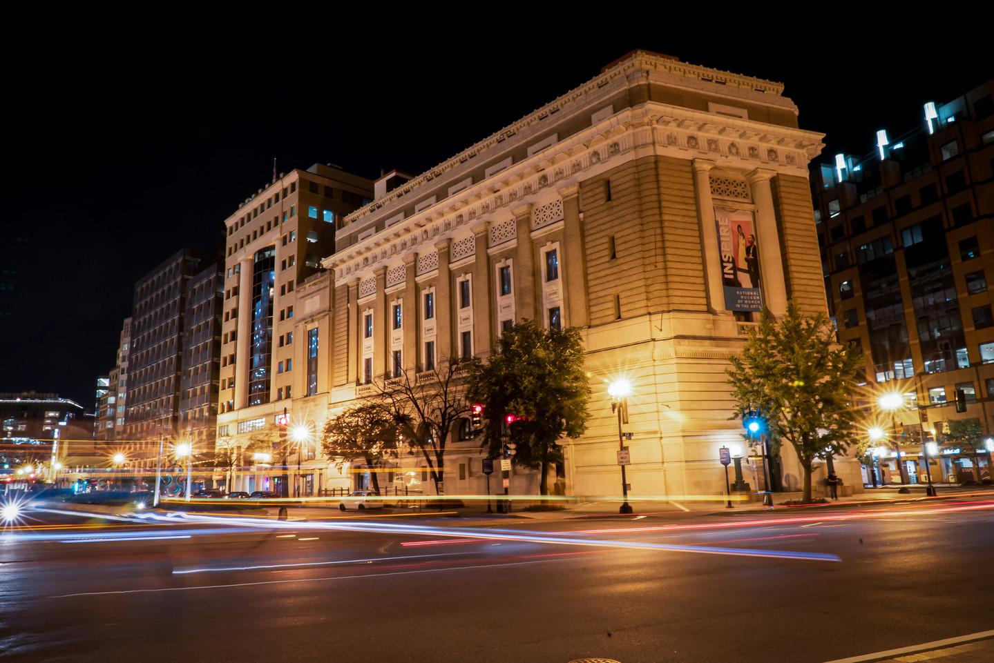 Nighttime photograph of the building exterior with car lights streaking in the foreground.