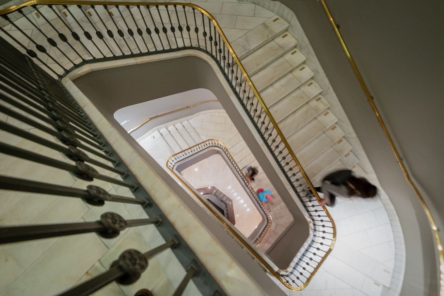 Photograph of the stairwell taken from the top looking down as two people are walking down the stairs.