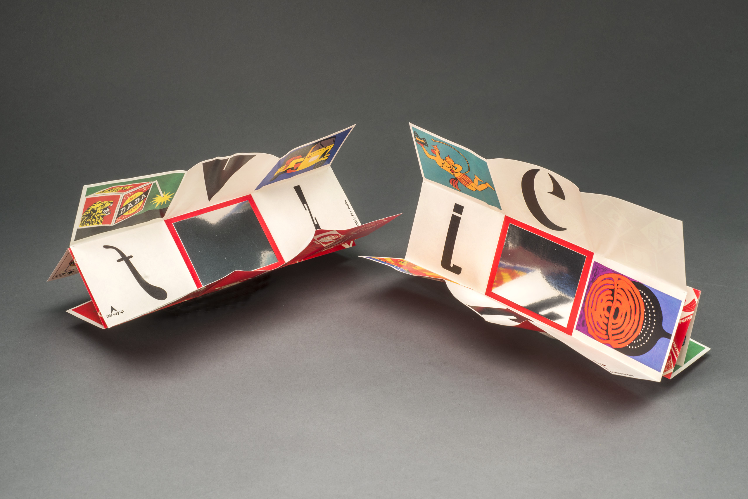 Two artists books with intricate folds and colorful panels sit side-by-side.
