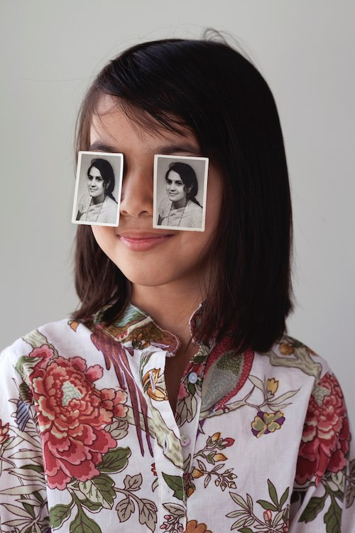 A portrait photograph of a girl with shoulder length straight dark brown hair, wearing a floral-print button-up shirt. She smiles slightly with her lips closed and atop her eyes are two identical black and white portrait photographs of a woman who is in a similar pose as the girl.