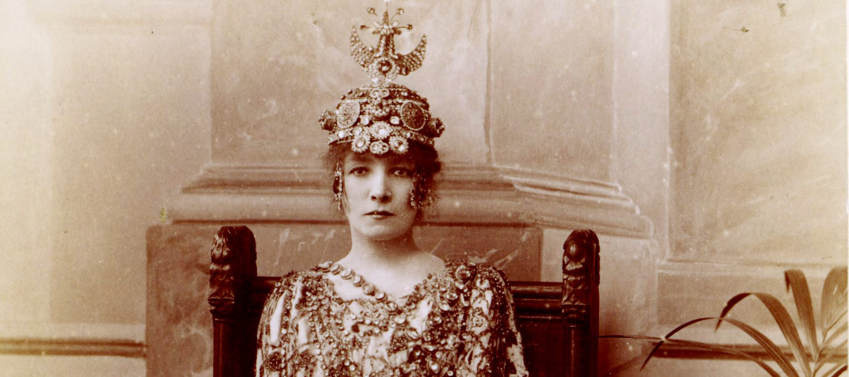 A sepia-toned photograph of a light-skinned woman dressed opulently in a beaded and patterned gown and wearing a beaded, luxurious headpiece.