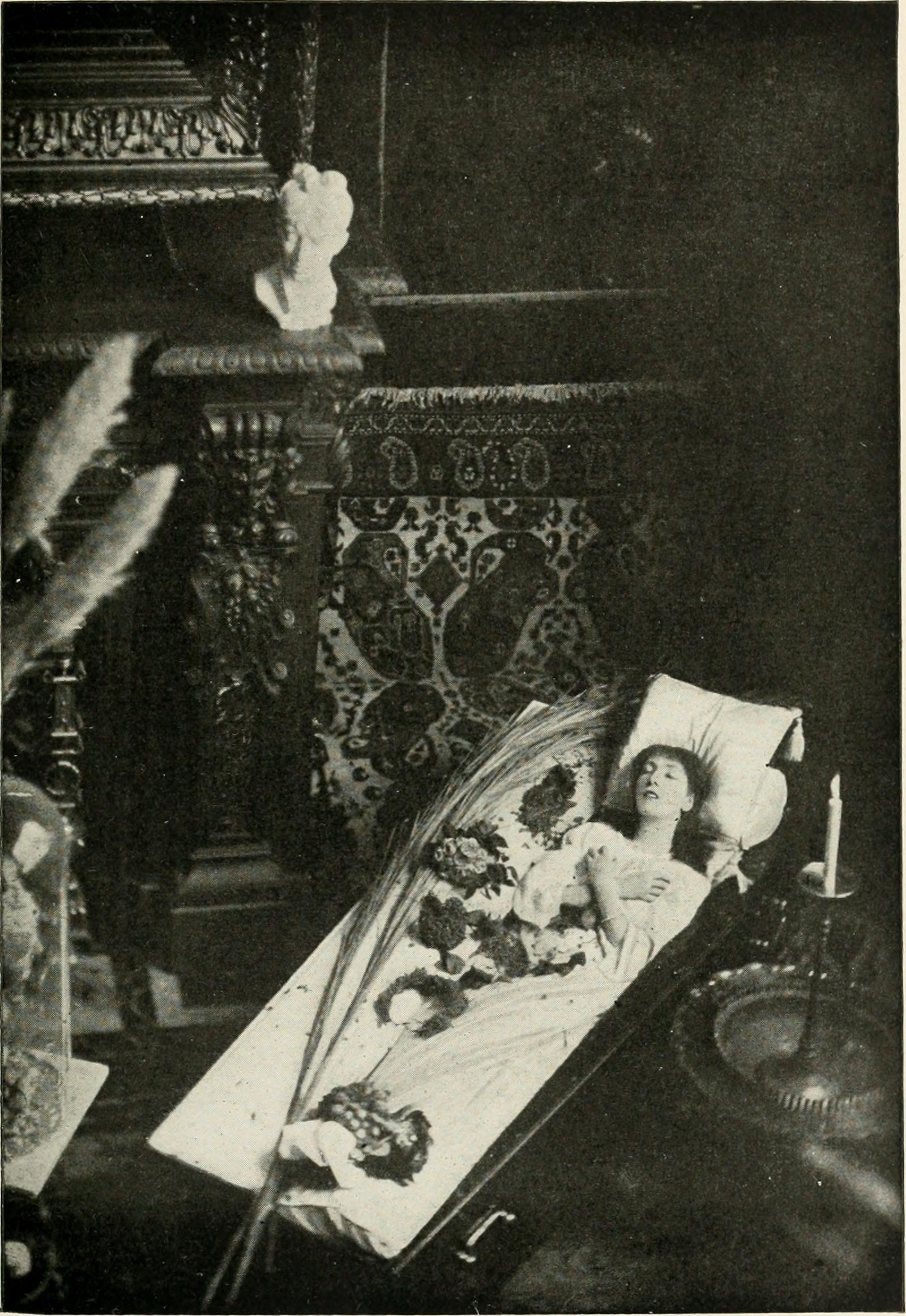 A black-and-white photo of a light-skinned woman laying in a coffin, plush with sheets and a pillow, in a room that had patterned tiled walls, a fireplace atop which a bust sits, and a fancy brass candle holder.