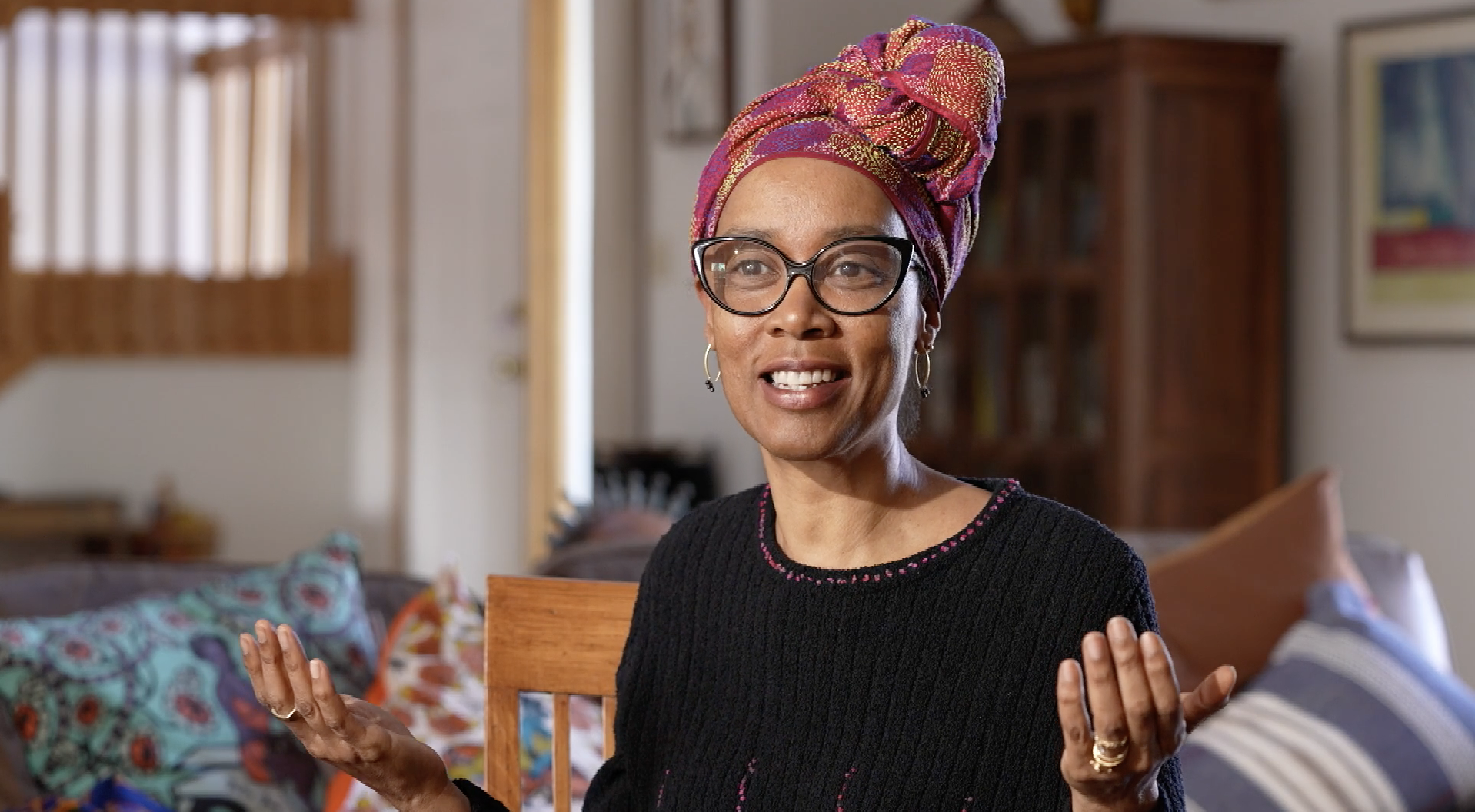 A dark-skinned women sits in a living room wearing a colorful headscarf knotted at the top; large, dark-framed glasses; and a long-sleeved black sweater. Her arms are stretched out at her sides with her palms facing up.