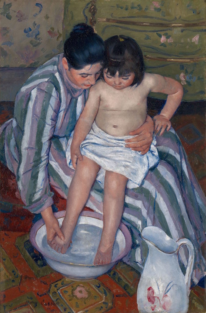 A painting of a light-skinned woman with black hair pulled back in a bun, wearing a long-sleeved striped dress, with a light-skinned little girl on her lap. The girl is nude, except for a white towel around her waist, and the older woman washes the girl's feet in a large porcelain bowl filled with water.