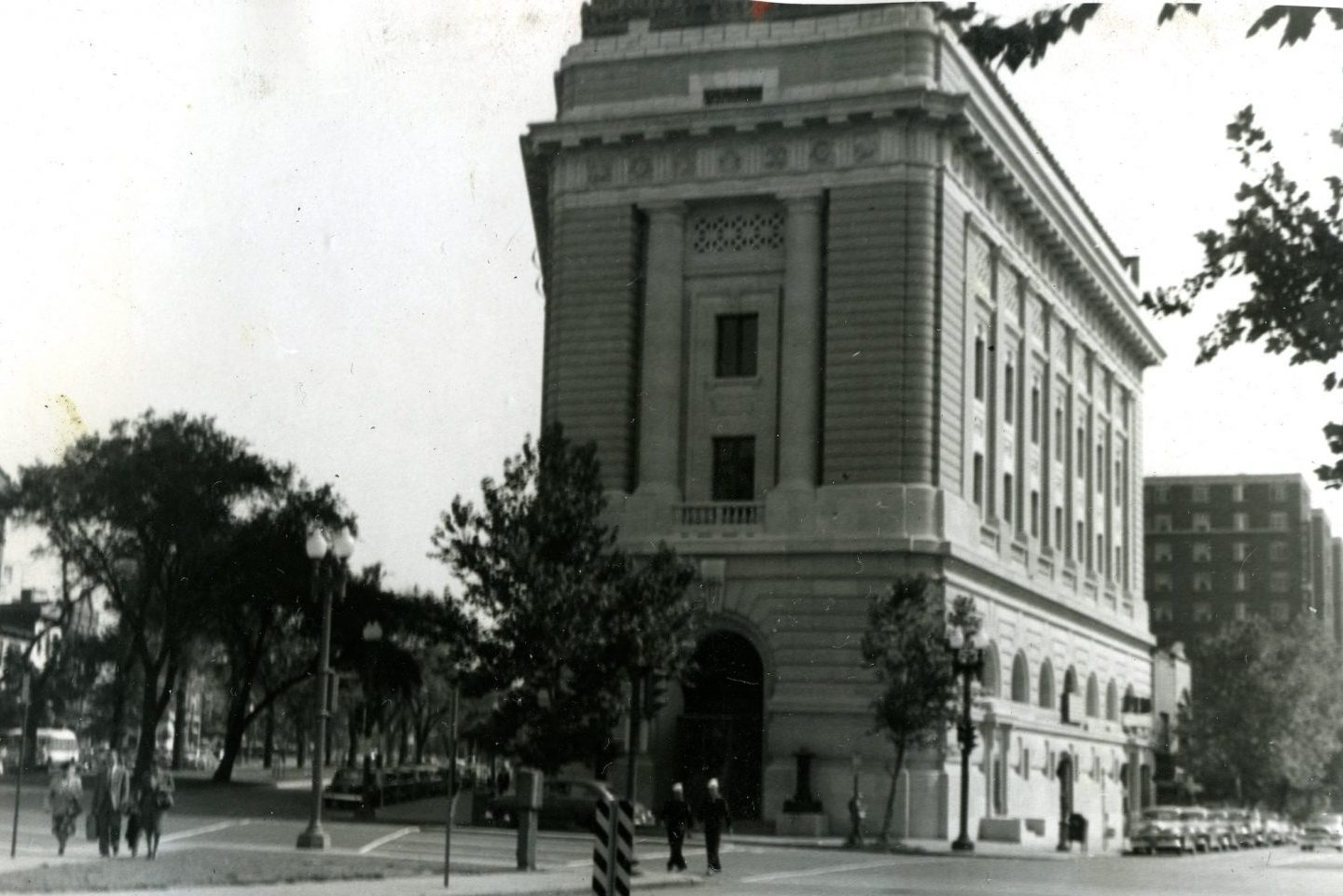 Black-and-white historic photograph of the building exterior with trees in the foreground.