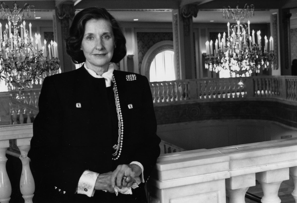 Black-and-white photograph of the museum founder, a white woman in a dark suit, standing on the Mezzanine level of the museum with her hands clasped as she leans against the marble railing in front of the Great Hall chandeliers.