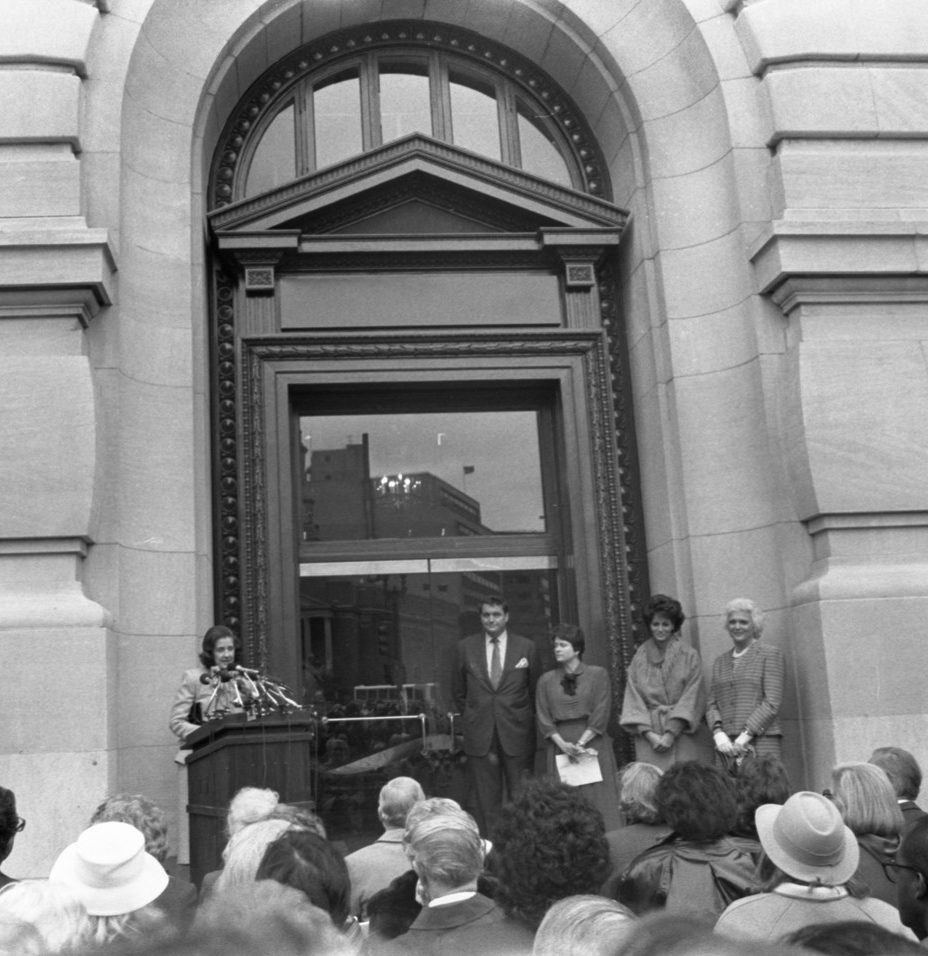A light-skinned woman speaks at a podium adorned with many microphones outside of a large building. A crowd of people look on and four others, three women and a man, stand in front of the crowd, to the side of the woman with their hands clasped in front of them.