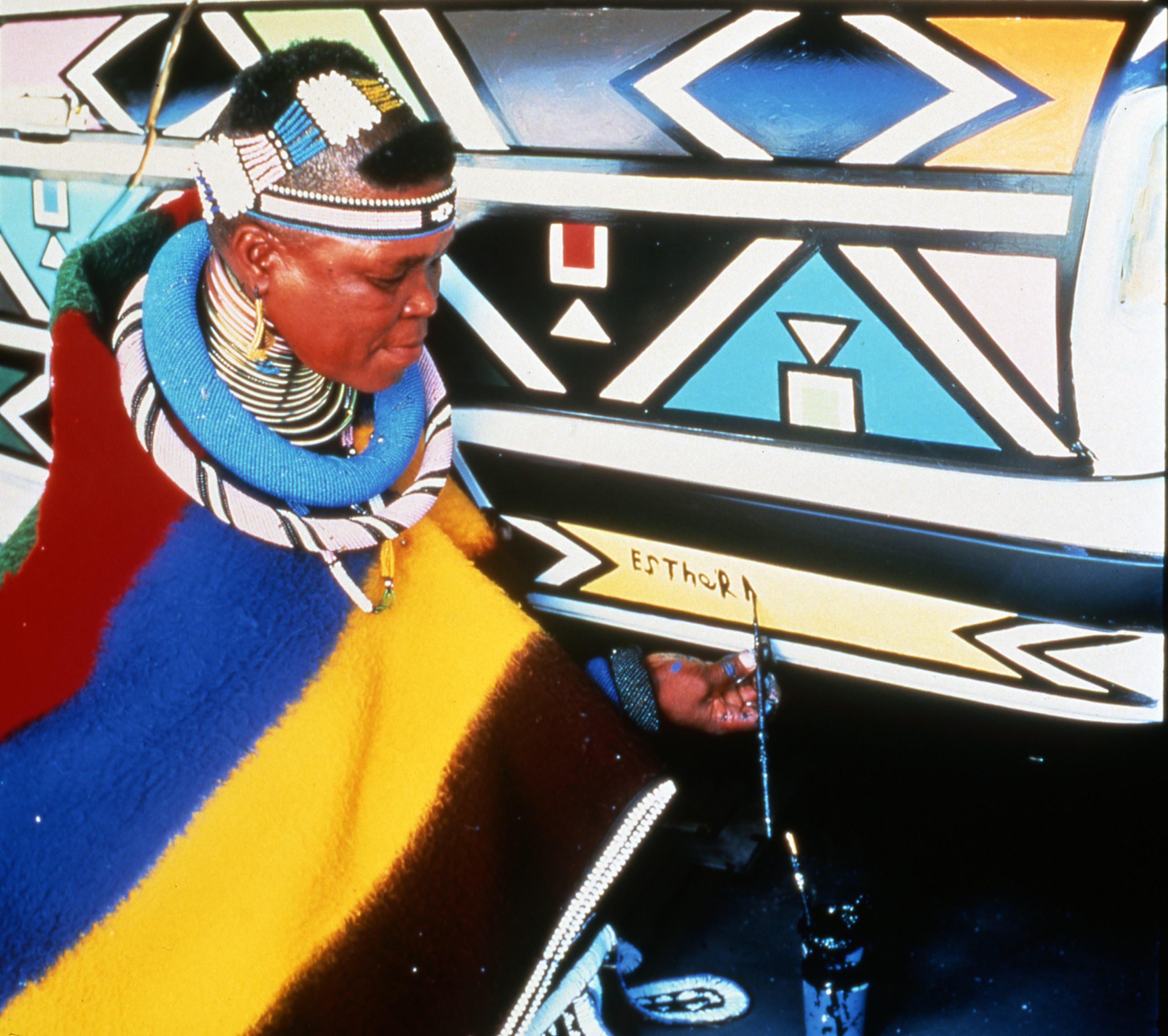 A dark-skinned woman wearing traditional African dress, paints her name on a car featuring colorful, geometric designs.