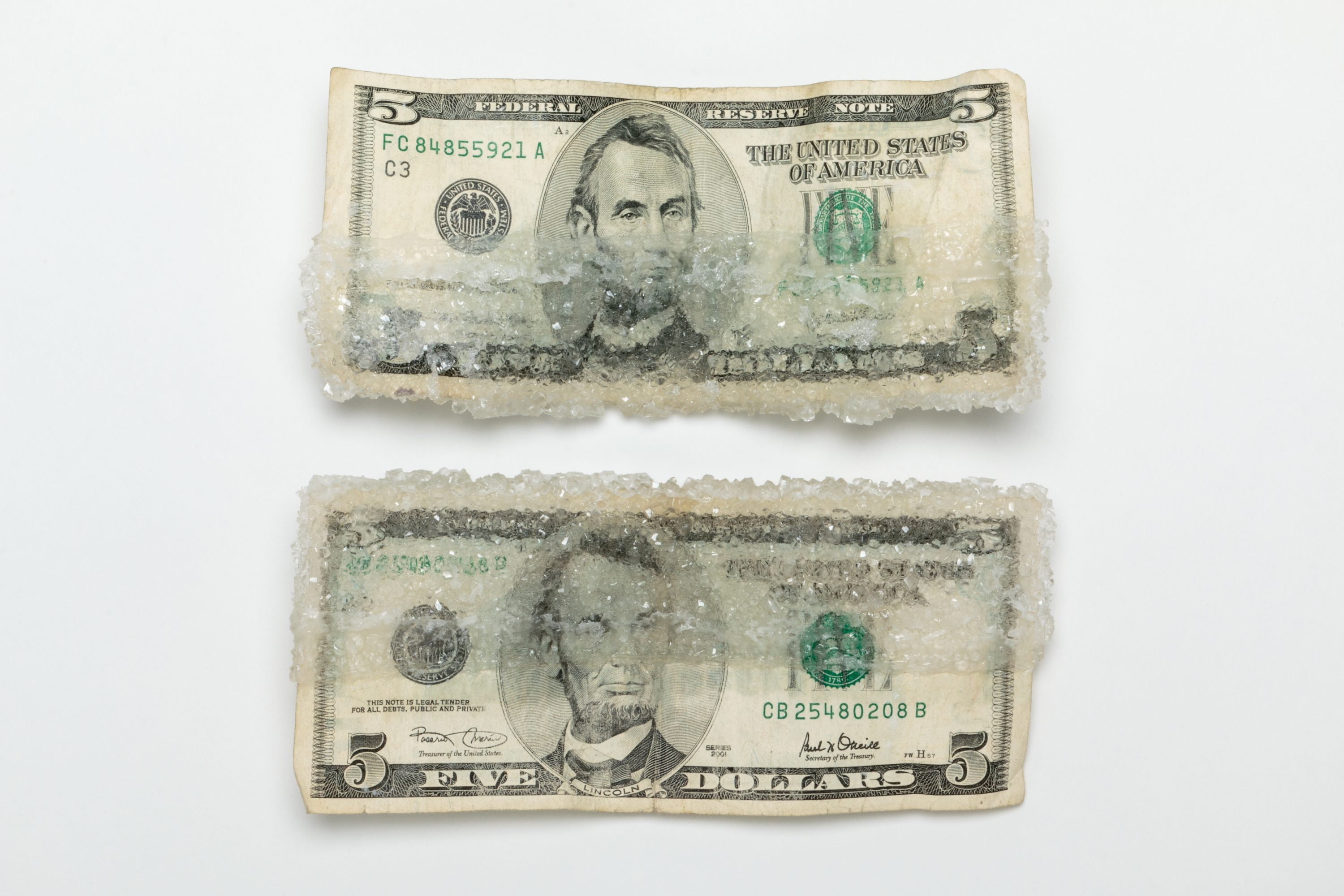 Two five dollar bills lay atop a white background. On the top bill, thick crystals of sugar encrust its lower half; on the bottom bill, thick crystals of sugar encrust its upper half.