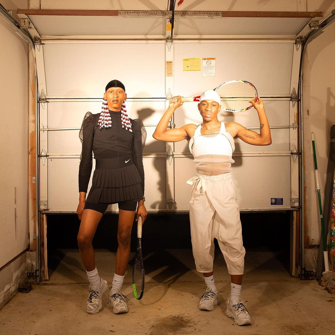Two dark-skinned people stand in front of a garage door that is open slightly toward the bottom, revealing darkness. One is dressed all black, a tennis skirt, bike shorts, and long sleeve shirt, a du-rag and red and white beaded braids. The other person is dressed in white and khaki pants and a tank top, a white du rag, and holds a tennis racket above their head.