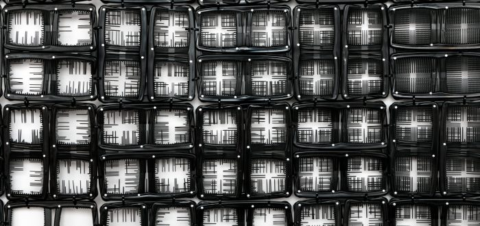 A detail photograph of black pocket combs arranged into a gride of squares. In some squares, the teeth have been snipped so the background is white, in others select teeth are left creating fine black lines. Still in others squares, the majority of teeth have been left creating a predominately black background.