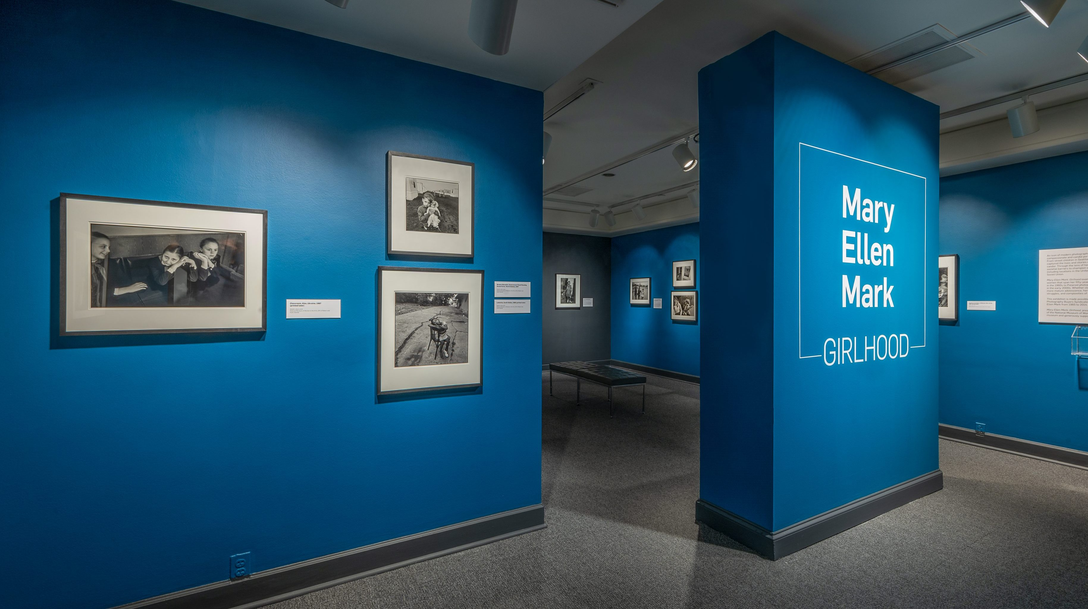Gallery view of black-and-white photographs hung against blue walls.