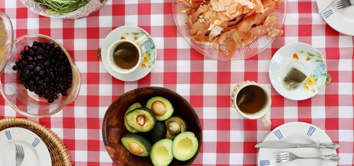 Circular glass, wood, and ceramic plates and bowls arranged on a red and white checkered tablecloth, seen from above. The plates and bowls are filled with blueberries, long carrot stems, halved avocados, an onion and onion peels, and a cups of tea and teabags on saucers.