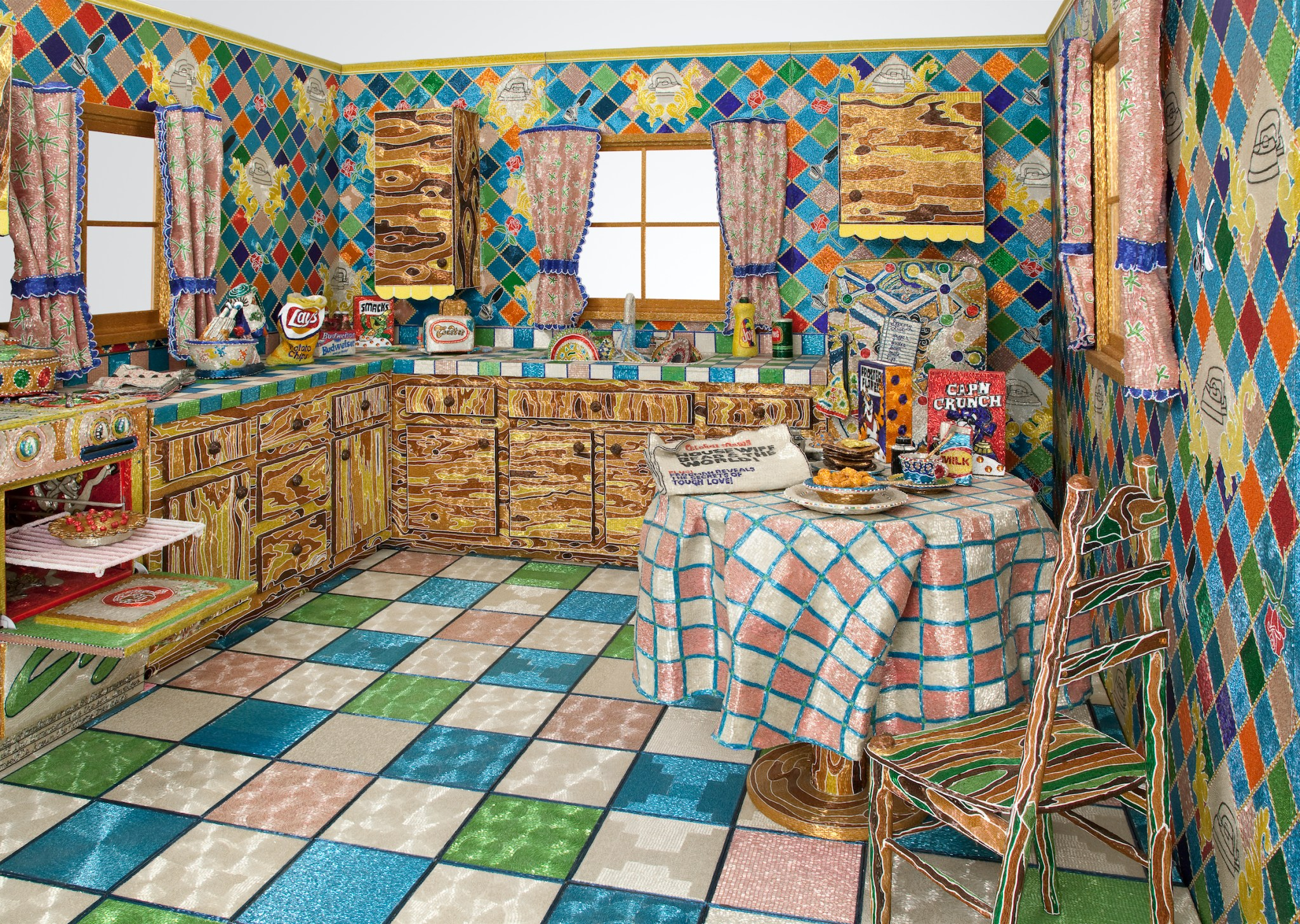 A colorful recreation of a traditional, homey kitchen made from glass beads and wire, complete with an open oven and a table that holds a box of Captain Crunch, a breakfast plate, and a newspaper.