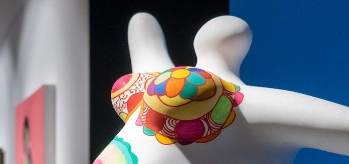 A white clay sculpture that depicts the headless pregnant body of a woman with her arms extended out. Her belly and breast are painted in a multi-colored pattern.