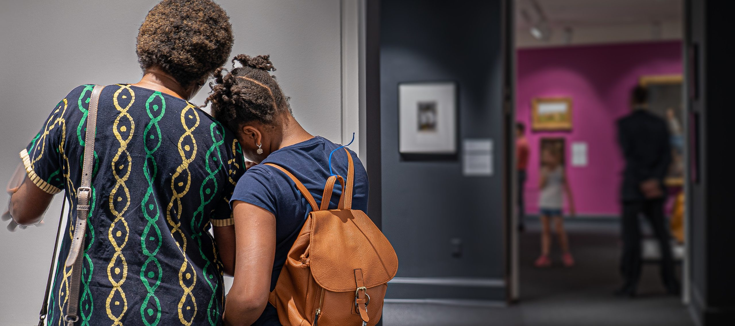 A middle aged, medium dark-skinned woman and a school age medium dark skinned girl face away from the camera and lean into each other affectionately while viewing artwork.