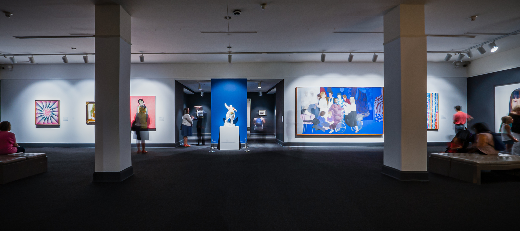 Wide angle view showing a full gallery. The floor is a dark gray carpet and there are two columns, through which large scale works in vibrant colors are visible.