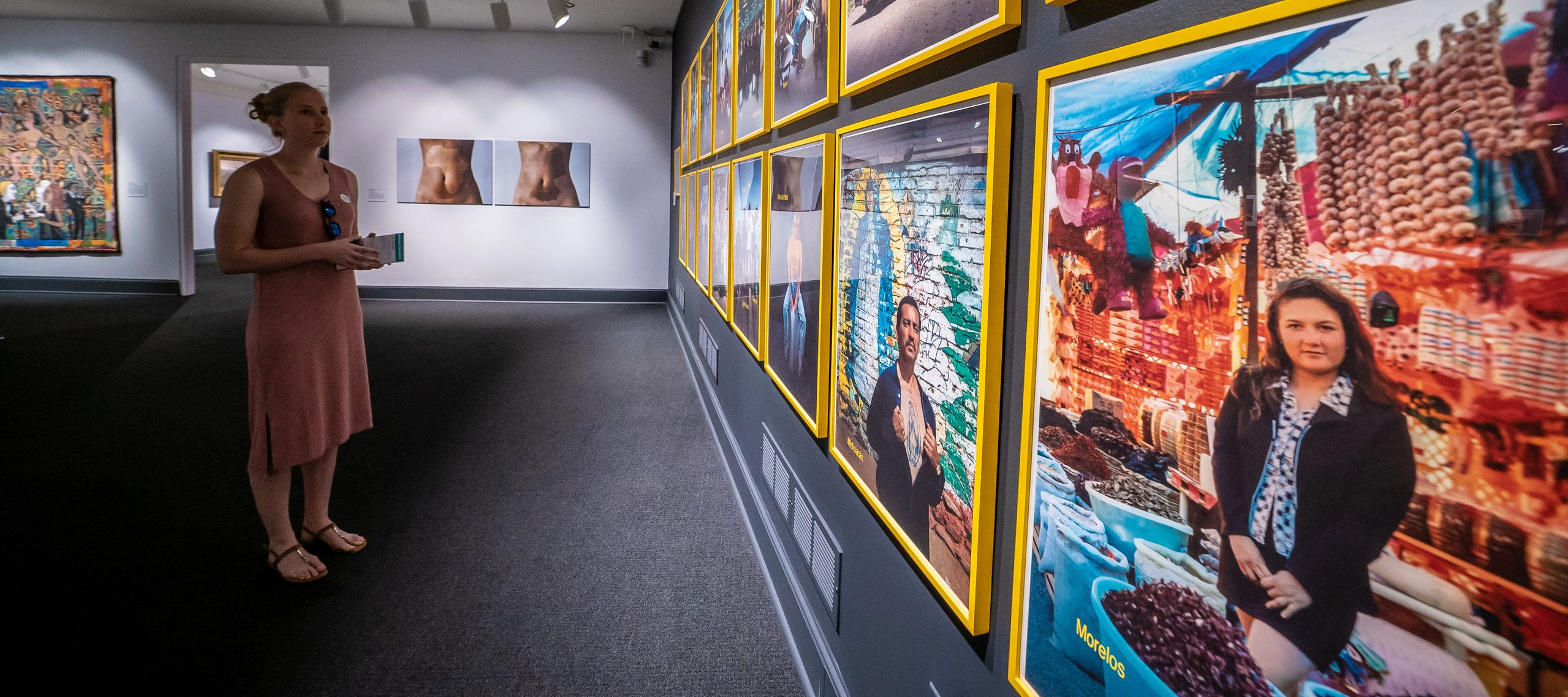 Gallery view of a person with light skin looking at a wall of photographs in bright yellow frames. Two artworks hand on the far wall.