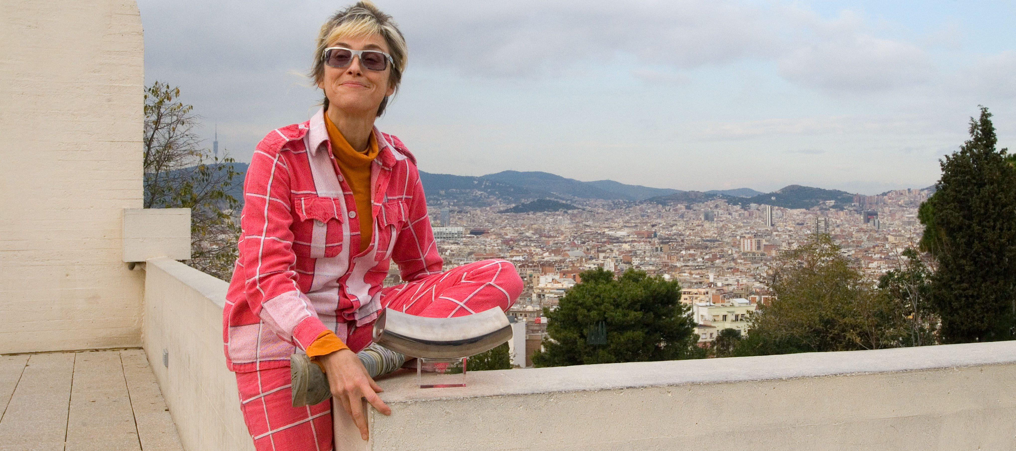 A light-skinned woman with a blonde and brown pixie cut sits atop a cement wall that overlooks Barcelona. She wears a dark and light pink cardigan and pants with checkered white lines over an orange turtleneck. She sits casually on the wall with one left folded under her and the other long, touching the ground. She smiles mischievously at the camera.